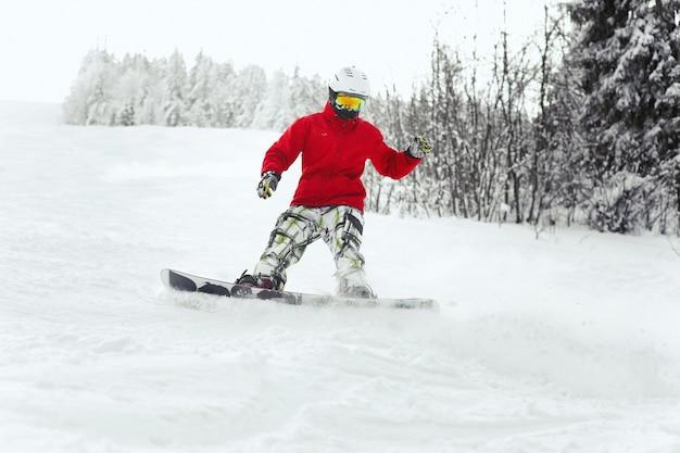 Mira desde abajo al hombre que desciende en el snowboard a lo largo de la línea del bosque