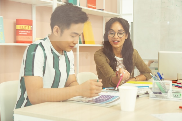 Mira aquí. estudiante asiático atento que está en todos los oídos mientras escucha a su compañero de clase