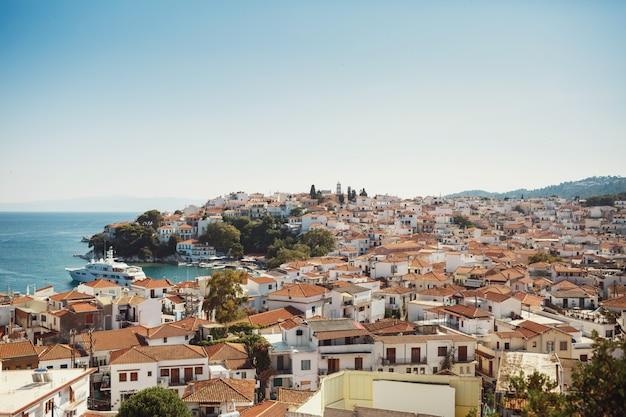 Mira desde arriba en la hermosa ciudad griega en los rayos de luz de verano
