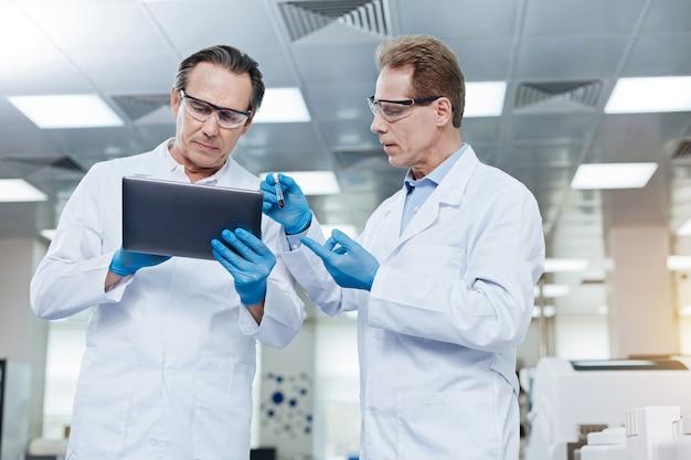 Mira este. asistente de laboratorio competente que usa gafas protectoras mientras está de pie en posición semi y muestra el tubo de ensayo con sangre a su colega
