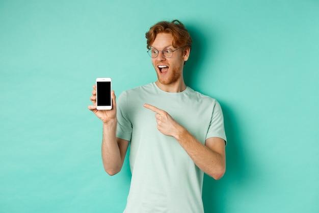 Mira esto. chico guapo pelirrojo con gafas apuntando con el dedo a la pantalla del teléfono inteligente en blanco, mostrando la promoción en línea, de pie asombrado sobre fondo turquesa.