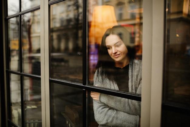 Mira desde el exterior a una encantadora mujer de pie pensativa detrás de la ventana