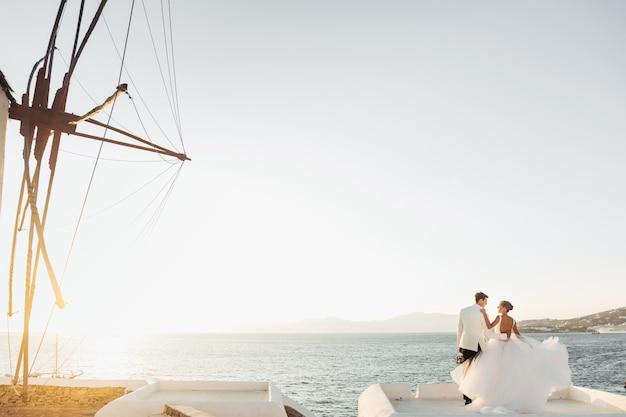 Mira desde lejos a la encantadora pareja de novios mirando la puesta de sol sobre el mar