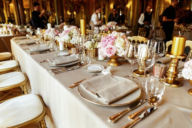 Mira desde lejos a la mesa servida con ricos cubiertos y vajilla, jarrones de oro y candelabros
