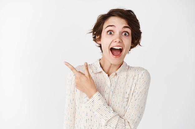 Mira esto, mira. emocionada chica morena apuntando con el dedo a la izquierda con cara de sorpresa, de pie sobre la pared blanca