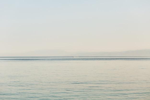Mira desde la orilla en el mar sin fin y el barco en él