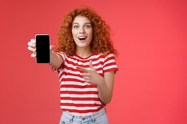 Mira qué teléfono inteligente increíble. impresionado emocionado, atractivo, amor femenino, innovaciones digitales, pelirroja, niña, peinado rizado, que muestra la pantalla del teléfono, que señala la pantalla, promueve una aplicación genial.