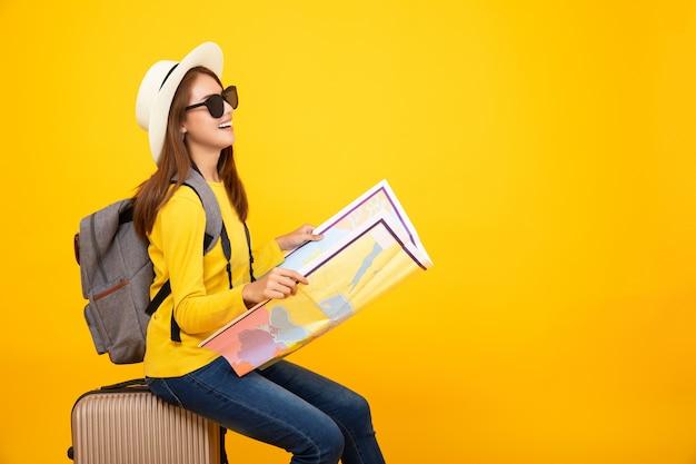 Mirada asiática turística de la mujer en el mapa con el bolso en el fondo amarillo