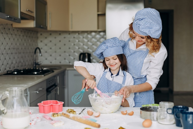Mirada familiar hija y su madre rompen un huevo con una sonrisa.