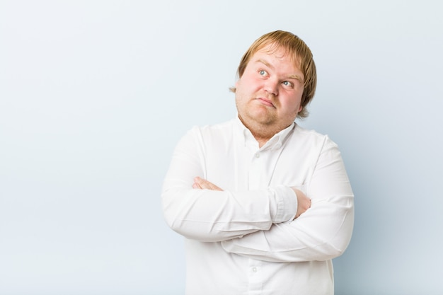 Mirada infeliz del hombre gordo del pelirrojo auténtico joven in camera con la expresión sarcástica.