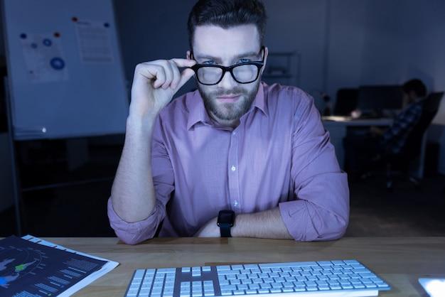 Mirada inteligente. hombre guapo encantado inteligente sentado frente a la computadora y arreglando sus gafas mientras te mira