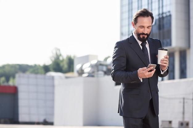 Mirada profesional alegre apuesto hombre de negocios que va a hacer una llamada mientras toma café