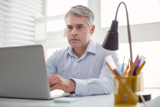 Mirada seria. hombre inteligente agradable seguro sentado en la mesa y mirando la pantalla del portátil mientras trabaja
