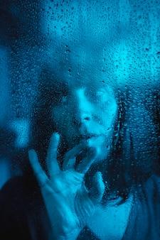 Mirada triste de una joven mirando una noche lluviosa