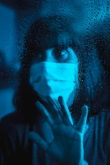 Mirada triste de una joven mujer caucásica mirando una noche lluviosa en la cuarentena de covid19