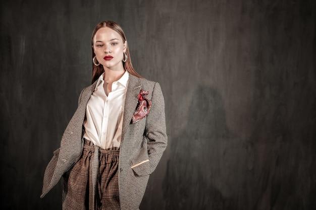 Mírame. modelo de moda profesional que demuestra un elegante abrigo, de pie sobre una pared gris