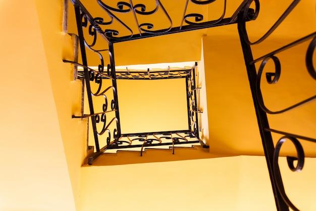 Mirando hacia abajo una escalera de tres pisos