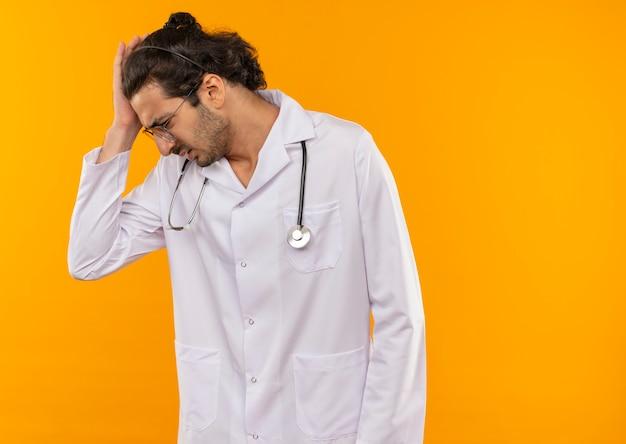 Mirando hacia abajo joven médico con gafas médicas vistiendo bata médica con estetoscopio en cuestión poniendo la mano en la cabeza