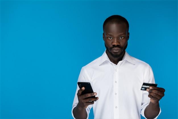 Mirando hacia adelante hombre afroamericano tiene tarjeta de crédito y teléfono celular en manos