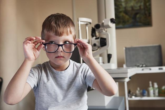 Mirando al costado. retrato de niño sentado con gafas en la clínica del médico con equipo oftálmico