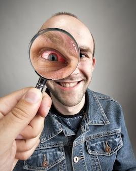 Mirando al hombre sonriente divertido con ojos enojados a través de una lupa