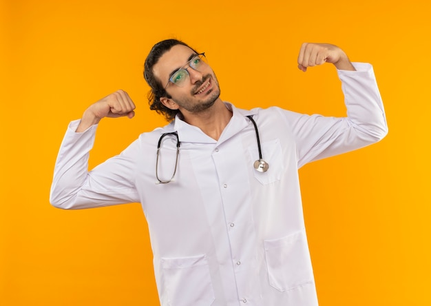 Mirando al lado complacido joven médico con gafas médicas vistiendo bata médica con estetoscopio mostrando un gesto fuerte