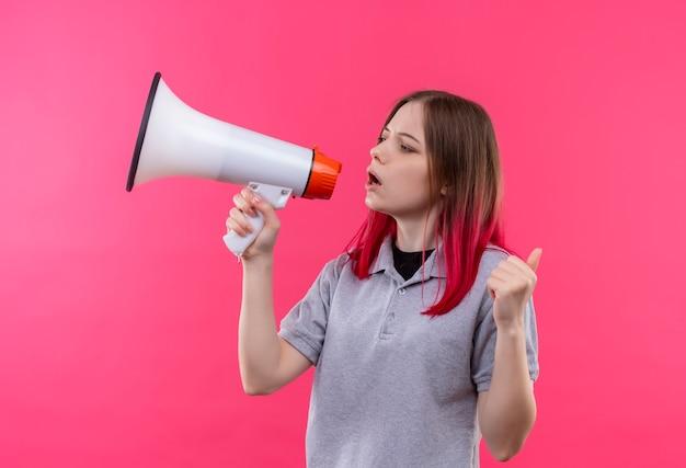 Mirando al lado hermosa joven vestida con camiseta gris hablando a través de altavoces sobre fondo rosa aislado