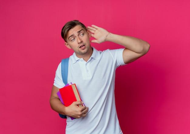 Mirando al lado joven apuesto estudiante masculino con mochila sosteniendo libros y mostrando escuchar gesto aislado en la pared rosa