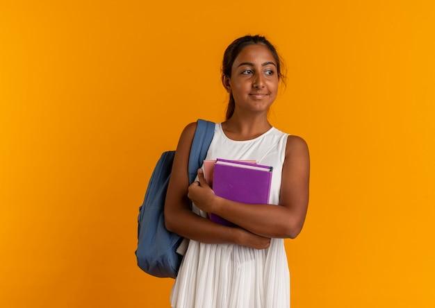 Mirando al lado joven colegiala con mochila sosteniendo libros