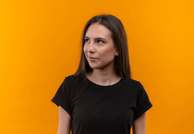 Mirando al lado sonriente joven caucásica vistiendo camiseta negra sobre pared naranja aislada