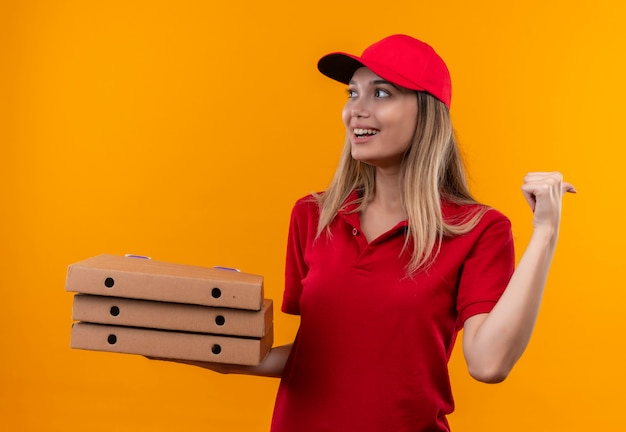 Mirando al lado sonriente joven repartidora vestida con uniforme rojo y gorra sosteniendo la caja de pizza y apunta al lado aislado sobre fondo naranja