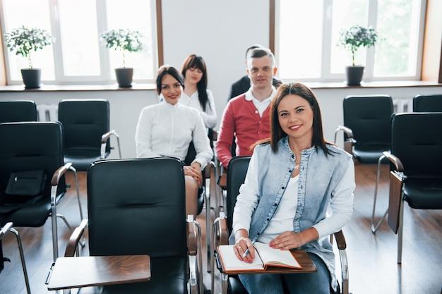 Mirando a la cámara. grupo de personas en conferencia de negocios en el aula moderna durante el día