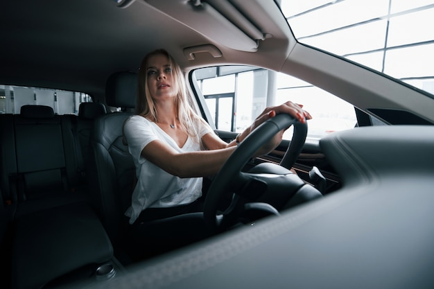 Mirando en el espejo. chica en coche moderno en el salón. durante el día en interiores. comprar vehículo nuevo