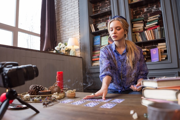 Mirando hacia el futuro. mujer joven inteligente teniendo una sesión de adivinación mientras la graba en video