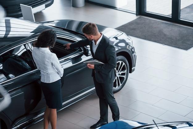 Mirando el interior del vehículo. clienta y empresario barbudo con estilo moderno en el salón del automóvil
