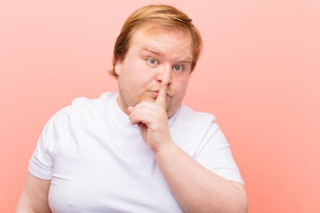 Mirando serio y enfadado con el dedo presionado contra los labios exigiendo silencio o silencio, guardando un secreto