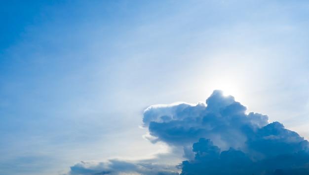 Mirando a sun detrás de la nube con cielo azul