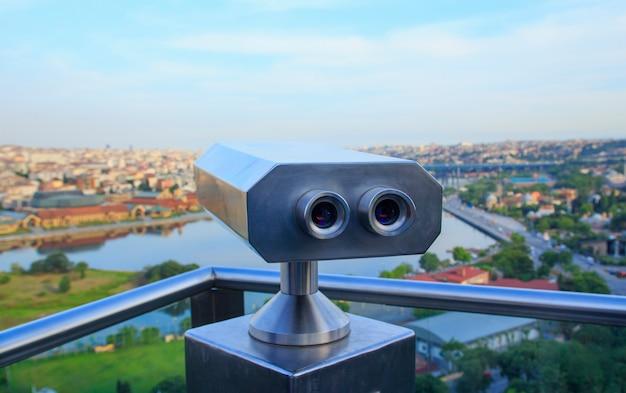 Mirando a través de binoculares al atardecer en estambul