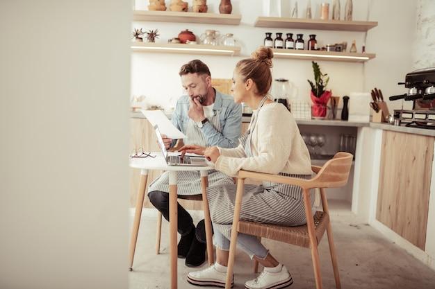 Mirando a través de biografías. marido y mujer concentrados sentados junto a la computadora portátil en busca de mano de obra para su cafetería familiar.