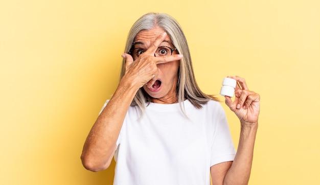 Mirar conmocionado, asustado o aterrorizado, cubrirse la cara con la mano y mirar entre los dedos y sostener un frasco de pastillas