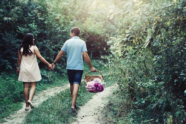 Mire por detrás a una pareja encantadora, tomados de las manos mientras camina por el camino