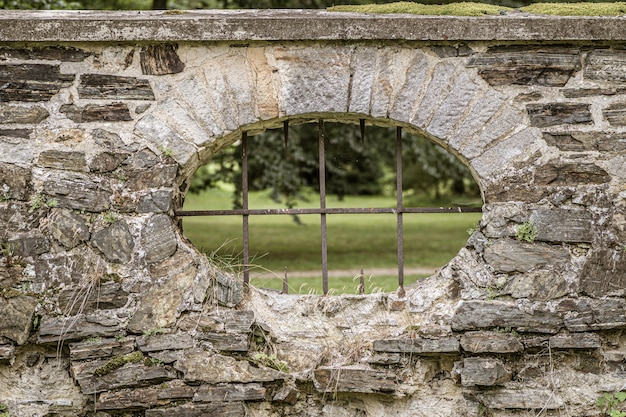 Mirilla con barras de hierro en una valla de piedra