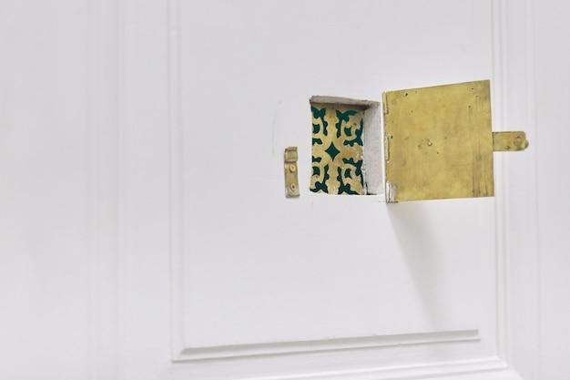 Mirilla dorada de metal antiguo vintage en la puerta de entrada.