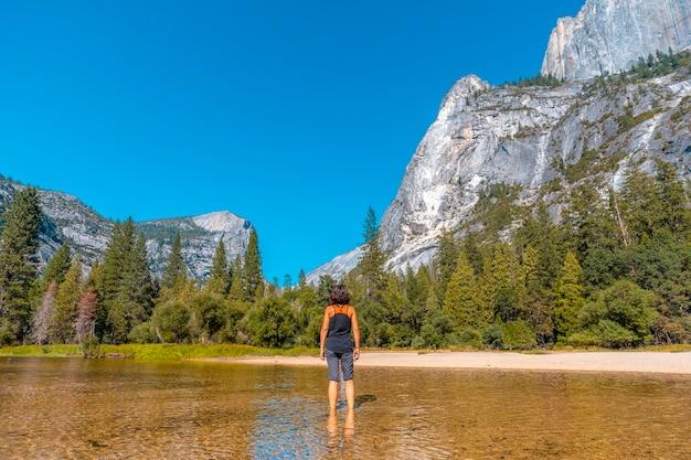 Mirror lake, una mujer joven con una camisa negra en el agua del lago. california, estados unidos