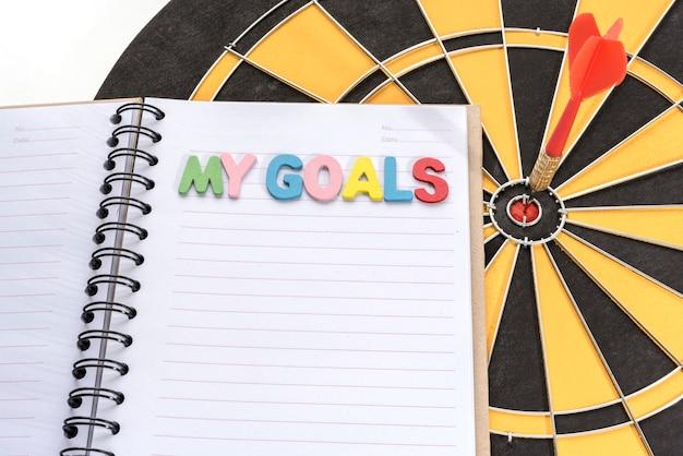 Mis metas en el cuaderno con dardo objetivo de fondo