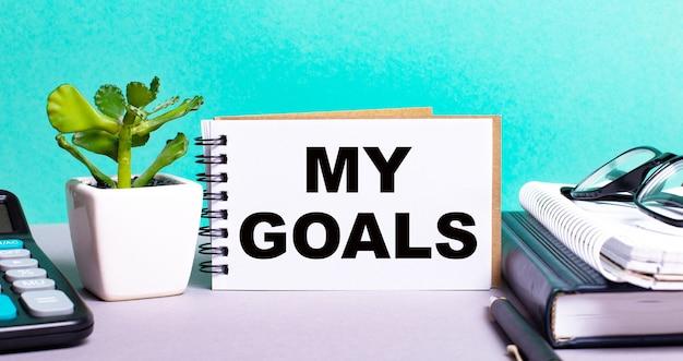 Mis metas está escrito en una tarjeta blanca junto a una maceta de flores, diarios y calculadora. concepto organizativo