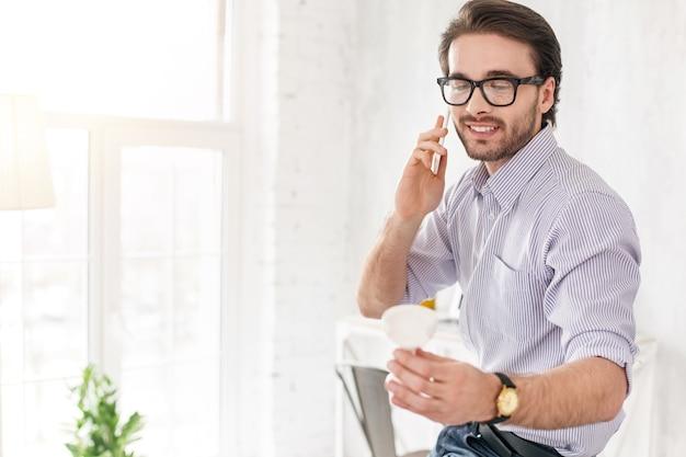 Mis metas. hombre alerta guapo hablando por teléfono y sosteniendo un objeto blanco