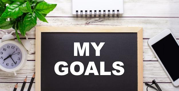 Mis objetivos escritos sobre un fondo negro cerca de lápices, un teléfono inteligente, un bloc de notas blanco y una planta verde en una maceta