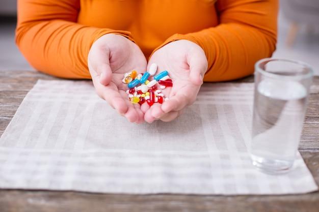 Mis pastillas. mujer gorda sentada en la mesa y sosteniendo pequeñas píldoras de colores