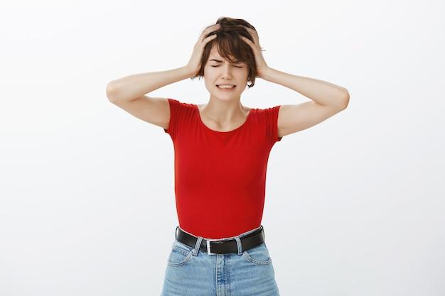 Miserable mujer llorando con situación complicada, moviendo la cabeza frustrada
